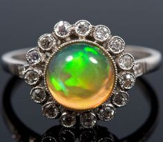 Ladies' opal and diamond cluster cocktail ring with central opal surrounded by fifteen diamonds in millegrain setting.