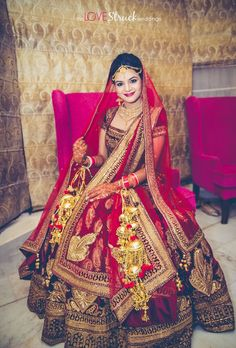 The gorgeous Indian bride posing in her maroon and gold velvet lehenga.