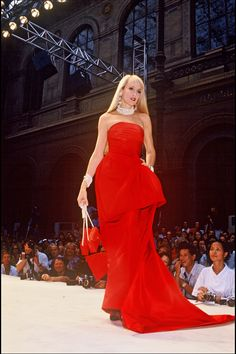 Jerry Hall on the runway. She's wearing a red strapless dress with a train and a sash at the hip. 1986.