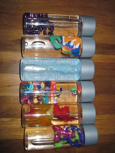 Inside the bottles:    From the top    1. water and a beaded neckalce    2. water and foam numbers and letters    3. water and glitter    4. water and mixed beads    5. water and nature elements (rocks and fake leaves)    6. water and ribbon