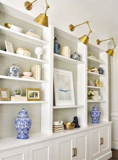 Brass sconce lights over built in shelves.