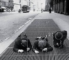 1930, Three boys fish for change in the street grates of New York during the depression.