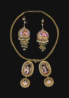 A QAJAR GOLD AND ENAMELLED NECKLACE AND EARRINGS, PERSIA, 19TH CENTURY comprising a gold necklace with two hanging pendants each composed of an oval diamond-set frame featuring an enamelled portrait of a young male and female figure, each with a hanging roundel framing an enamelled face, the earrings made up of two domed elements and a pendant drop, decorated with polychrome enamel flowers and fringed with seed pearls