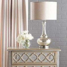 Deceptively simple, this classic table lamp is exceptionally stunning. It's gourd shape is embellished with a silver and gold crackle metallic finish, a round chrome metal base, and a round hardback fabric shade.