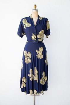 Vintage 1940s cotton shirt dress: bodice has buttons down the center, a v-neckline, and a slight collar detail. Short sleeves, belted waist,  flared skirt.