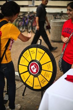 A student spins the prize wheel to win school supplies or refreshments at the Philanthropy Awareness Day event Tuesday. (http://PrizeWheel.com/products/tabletop-prize-wheels/tabletop-black-clicker-prize-wheel-12-slot/)