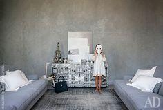 Дочь хозяйки Летиция позирует в венецианской маске вгостиной. Диваны Raffles, DePadova; комод, Fornasetti; стул, Cassina; старинный ковер, Sartori.