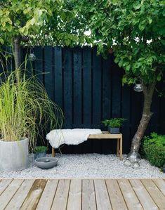 Foto: sfeervolle zwarte schutting icm steentjes en houten vlonders. Geplaatst door BrendaB op Welke.nl