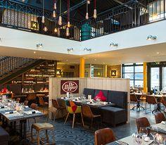 Interieur restaurant à Rouen avec tapis gris, tables en bois et chaises marrons