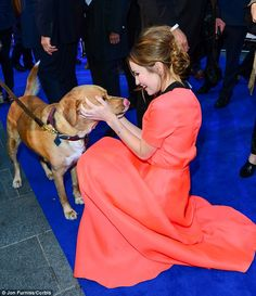 Girl's best friend? Tom also introduced the world to his beloved dog Woody, who Emily looked to be particularly attached to as she played around with him on the blue carpet