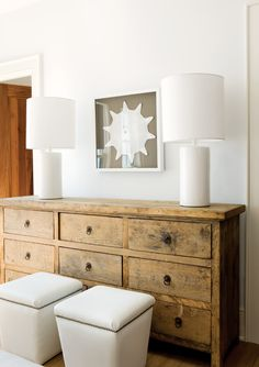 Love the rustic dresser with the modern lamps and art.