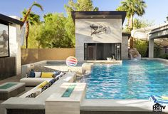 The Property Brothers' Las Vegas Home Pictures | POPSUGAR Home, But the home's main attraction is, of course, the epic pool area. The travertine-tiled fire pit keeps the party going after sundown, while the swim-up bar and motorized, drop-down screen can be enjoyed at any hour. The sculpture is a clock.