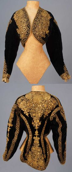 Midnight blue bolero-style jacket, with peplum, ca. 1870. Silk velvet heavily decorated in metallic gold cord and sequins in an ethnic style. Lace-trimmed sleeves and silk lining. Purportedly bought from House of Worth as fancy dress.