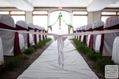Wedding ceremony aisle decoration at WeaverRidge Golf Course.  White aisle runner with white chair covers and burgundy satin sashes.  Clean and simple wedding decoration on a budget.