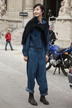 Combinaison en jeans, bottes en cuir noir et pull sur les épaules, puis les cheveux noirs et la peau blanche.
