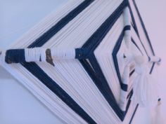 """One of a kind, handmade Navy blue and cream """"God's Eye"""" wall hanging with tassels and wooden beads.   This is a modern tribute to Ojo de Dios; God's Eyes are not only beautiful but can serve a purpose in every day spiritual work.  """"The Ojo de Dios or God's eye is a ritual tool, magical object, an..."""