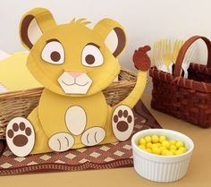 Simba Cub Tabletop Decoration. Fashioned from paper party plates, this cute cub card basket makes a lively addition to a baby shower gift table.