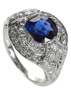 *An Art Deco platinum, sapphire and diamond ring, featuring a square cushion-cut blue sapphire with an approximate total weight of 1.55 carats surrounded by Old European-cut diamonds of approximately .80 carat.
