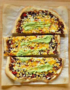 southwestern pizza with black beans and corn! pizza dough, black beans, adobo, chili, cumin, salt, olive oil, tomato, onion, corn, monterey jack and cheddar cheeses, avocado (no thank you), sour cream, and lime juice. NOM.