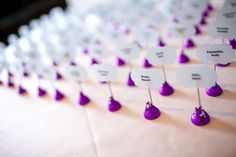 Quick & easy escort cards! Just print the guest's name on a clear label, stick it onto a cardstock shape in the color of your choice, hot glue it onto one end of a toothpick (or something similar), and stick the other end into a Hershey's Kiss! Arrange on a table and voila, inexpensive (but totally delicious) escort cards!