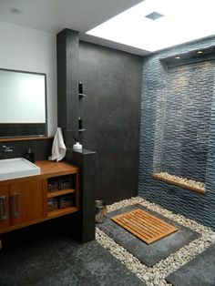 Balinese modern bathroom _ Gerson Residence by Susan Thiel Coon. => 8 feet skylight => river rock => hidden shower drain => limestone / teak finishes: