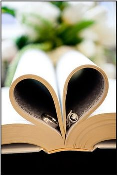 A different wedding photo shot with the bible pages folded in to form a heart and the wedding rings tucked inside.