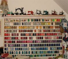 Wall of colorful threads topped with a shelf for displaying antique/toy sewing machines.