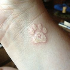 White ink heart in paw print tattoo on wrist