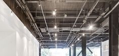 exposed ceiling showing lighting grid and ductwork
