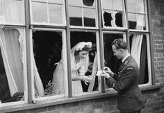 Warrant Officer Antoni Markiewicz of No. 302 Polish Fighter Squadron and his bride Yvonne Munday inspecting what was left of their wedding presents after the wedding reception house was bombed while they were getting married at a church somewhere in Southern England ~