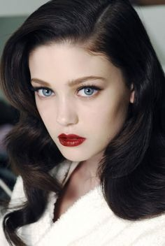 Black eyeliner on upper lids, long lashes, and red lips with dark, wavy hair (Diana Moldovan).
