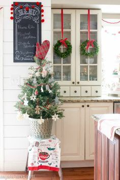 Small boxwood wreath hung with red ribbon and Kitchen Christmas tree displayed in olive basket