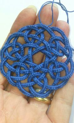 This is a Celtic knot, made from a tatting pattern, using the red, a tatting shuttle, and a world of patience.