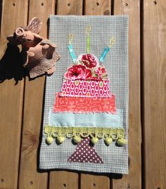 This is a creatively beautiful appliquéd celebration/birthday cake on an absorbent lightweight cotton towel. Looks great in kitchen or bath.