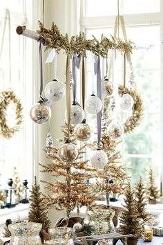 I do this every year, I love it! ornaments hung from a branch sourced from my own backyard - via Suzanne Kasler's holiday collection for Ballard Designs