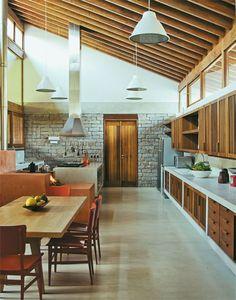 Cozinha rústica com ambientes divididos pelo fogão a lenha, chão de cimento, móveis de alvenaria e iluminação natural.