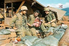 02 Jan 1968, Khe Sanh, South Vietnam --- 1/2/1968-Khe Sanh, South Vietnam- Marines sit admiring a pin-up, outside their bunkers at Khe Sanh, one of the Marines' key bases in the northern portion of South Vietnam. --- Image by © Bettmann/CORBIS