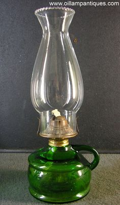 This green glass finger lamp is a bit of a mystery to us. We found it in a book that suggested it was German or Belgian circa 1910 but we're not so sure. The majority of the lamps from that region take a Kosmos burner rather than a flat wick burner. The collar is more like those used in North America but the style of the lamp and the colour of the green glass just doesn't have quite the right look to be from there. As we said, a bit of a mystery.