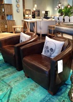 Black and white skull themed accent pillows give these beautiful brown leather chairs a creative edge.  Is this a style you would like to see in your home or in our stores? #hpmkt #hpmkt2014 #shopgf | Houston TX | Gallery Furniture |
