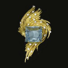 This is a gold, diamond & aquamarine brooch by Chaumet, ca 1970. I think I would've liked this better if the aqua was a round or oval cut. You have these sweeps of gold rendered feathers, a suggestion of a bird curling around the stone and then you have this hard edge, angular stone it's supposed to be embracing. It doesn't work. It looks uncomfortable and awkward, imo