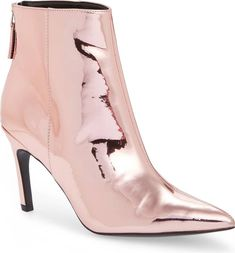 A dramatically pointy toe furthers the confident geometries of a wide-top bootie styled with an angled broken heel.