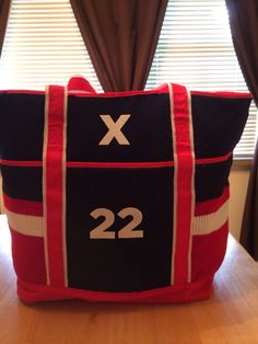 Refashion old bag to hockey mom bag. Stitched hockey socks over the bag. Letter and number are fleece stickers that are pre-cut. Sticks easily.