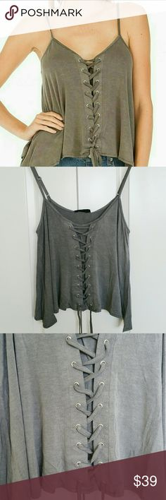 """Charcoal Lace Up Tank Top Charcoal lace up tank top with lace ties detailed.  Soft fabric and adjustable straps with lace ties.  Modeling size small.  True to size.   Brand new in original package.  Available in 4 solid colors - Charcoal, Olive,  Navy,  Dusty Pink.   Measurements Laying Flat : Small  Length - 26"""" w/the straps completely loose. Pit to pit - 17"""" Tops Tank Tops"""