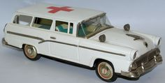 Vintage 1956 Tin Friction Powered Red Cross Ford Ambulance 2-Door Station Wagon by Bandai, Japan. Rear tailgate opens but is loose and needs to be set into place, and is missing the window above the t