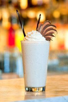 Naughty Frosty ~ Absolut Vanilla, Godiva White Chocolate Liqueur, Bailey's, vanilla bean ice cream & milk. Blended and served with whip cream and shaved chocolate garnish.