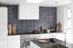 Stoere grijze tegel als achterwand in strakke witte keuken