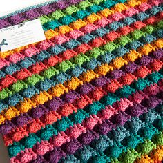 Blackberry Salad Striped Baby Blanket pattern by Tamara Kelly - free #crochet pattern! Big bright bobbles make this stunning textured blanket the perfect baby gift!