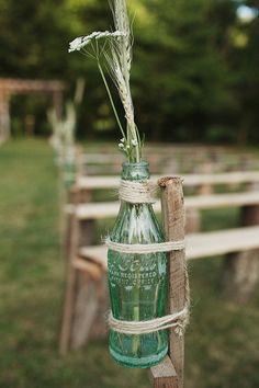 Des bouteilles de soda en verre ficelées à des piquets en bois avec une petite fleur des champs coriace. Fastoche.