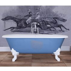 A traditional large cast iron bath shown painted in Farrow and Ball Cooks Blue with a set of four large traditional bath feet in white.