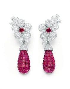 """A pair of """"mystery set"""" ruby and diamond """"Florets"""" ear pendant, by Van Cleef & Arpels. Photo: Christie's Images Ltd.., 2010    Each Designed as a circular-cut diamond flower, with a circular-cut ruby pistil Extending pear-cut diamond and marquise leaves, suspending a detachable calibrated drop-cut ruby topped by a circular-cut diamond cap, mounted in platinum and 18K white gold, with French assay marks and maker's mark, in a Van Cleef & Arpels navy blue suede box. Signed Van Cleef & Arpels"""